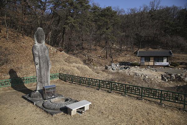 석불입상과 석불의 앞에는 석등의 좌대로 보이는 석조물이 있다.